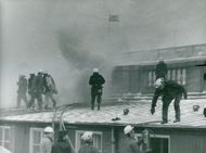 Firefighters carry out fire extinguishment on the roof of the Parliament House