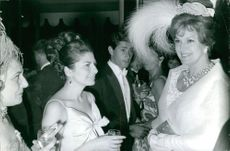 Soraya Esfandiary Bakhtiari talking to the women standing next to her in a party.