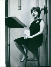Carol Sloane singing on a high chair.