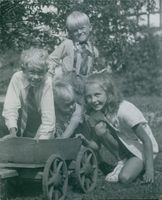 Taina Elg as a little girl posing with 3 little boys while playing with a mini sledge.