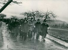 A crowd marching on a wet road.