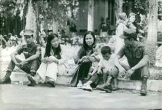 Soldiers sitting with women and children on sidewalk, in Vietnam. November 29, 1972,