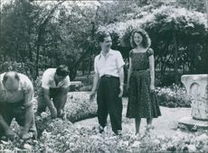 Peter II of Yugoslavia and Queen Alexandra standing in the garden and looking at the flowers plant with smiling face tended by the gardeners