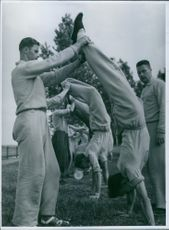 Men assisting other men to stretch body during training.