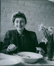 Woman having her meal and smiling while looking at the camera.
