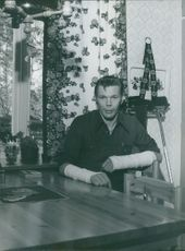 Man wearing bandages on both hands, sitting in the dining area.