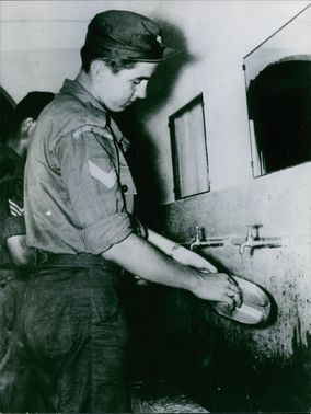 Constantine II, King of the Hellenes, washing dishes.
