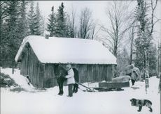 Women working beside their hut in the snow.
