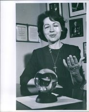 Jeane Dixon working on her crystal ball placed on the table.