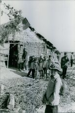 Group of villagers and children in front of hut during during the Vietnam war.