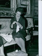 "A woman sitting on a couch and knitting.  ""of Claremont  daughter-in-law __ of Paris"""