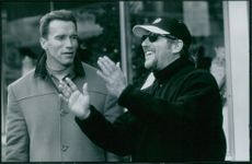 Brian Michael Levant and Arnold Schwarzenegger standing and talking to each other.