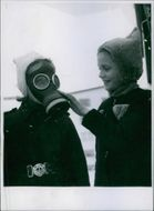 Two kids trying on a gas mask.