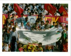 Kurds carry a huge banner with a picture.