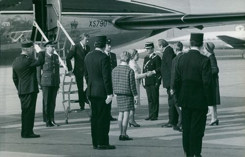 Princess Margaret standing with people at airport.