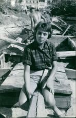 1961. A young lady sitting on a log..