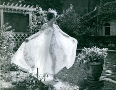 Gisele Pascal walking in the garden in costume.1961