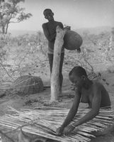 Tribal women, one is carrying a sack and the other one is weaving.