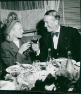 Maurice Auguste Chevalier having drink with a woman. Stockholm 1946