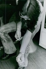"""A man injecting himself with drugs.  """"Draugs""""  1973"""