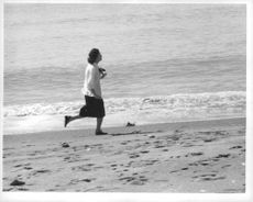 Princess Michiko running along the seashore.