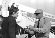 Yul Brynner talking to a man on airport.