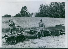 Damaged part of an airplane in the field, soldiers standing beside during Sweden War. 1942.