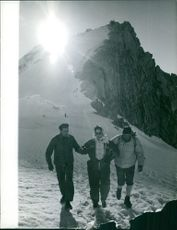 A woman walking with two men on a snowing field.