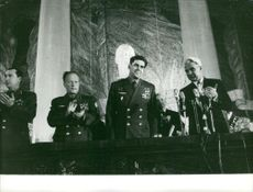 Pavel Belyayev with other men in uniform standing and clapping in a conference.  Taken - 7 Nov. 1968