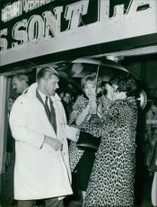 Princess Soraya standing under umbrella and talking to man.