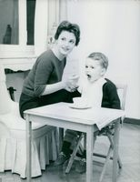 Rossana Podestà at home, feeding her only son, Stefano, three years old.