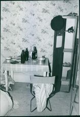 Indoor view of a room, wine bottle lying on the table.