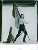 Woman standing and posing, holding flag and sword.