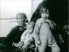 Woman with two children in boat.