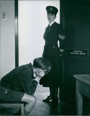 A woman officer standing and looking at juvenile criminal.