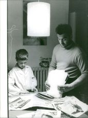 A man and a boy looking through magazines.