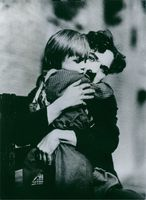 Charlie Chaplin embracing a child and looking towards the camera.