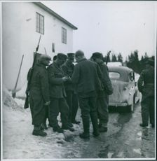 Soldiers standing together in a snowy street during Norway War, 1940.
