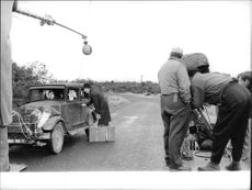 Danny Kaye standing beside car, being filmed, on set of Me and the Colonel.