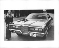 Woman standing beside Ford LTD 1971 car.