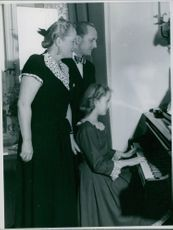 Einar Beyron with his wife Brita Hertzberg standing and looking their daughter playing piano. 1949