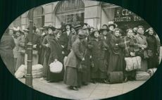 World War I 1914-18 People gathered in street, carrying luggage and talking to each other.