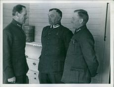 Officers standing together and communicating with each other. 1940