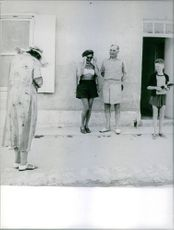 A woman posing with a man, another woman taking picture of them.