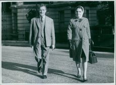 Man and woman walking on the road, holding attache.