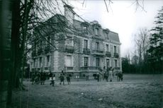 Children standing and playing with their teachers in front of a building.