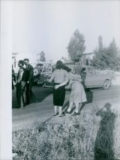 Woman supporting an old lady to walk, while a soldiers jeep passing.