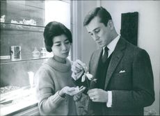 Man holding a flower in his hands, woman standing beside, talking to him and smiling.  1961 royalty laos