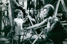 Michele Morgan interacting with a little girl.