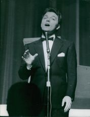 Dickie Valentine standing in front of the microphone, 1954.